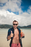 Nice young man holding a cold drink. In his left hand while showing the thumbs up gesture Royalty Free Stock Image