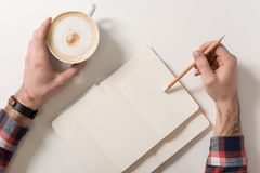 Nice young man holding a pencil. Waiting for inspiration. Nice young man holding a pencil and drinking his coffee while writing something in his notebook Stock Photos