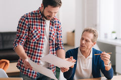Nice young man holding two sheets of paper. What to choose. Nice young bearded men holding two sheets of paper and deciding with his colleague which one to Royalty Free Stock Image