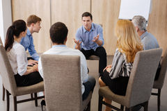 Nice young man talking to his colleagues. Team leader. Nice emotional young men talking to his colleagues and gesticulating while sitting in front of them Stock Photo