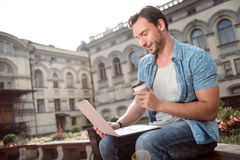 Nice young man using laptop. Busy. Cheerful young man sitting and using his laptop being outside and drinking coffee Royalty Free Stock Photography