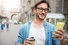 Nice young man using phone. Digital youth. Portrait of content and smiling young man listening music while having fun in the city, using earphones and holding a Stock Photography