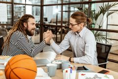 Nice young men doing armwrestling in the office. Who is stronger. Nice young men doing armwrestling while deciding who is stronger stock photography