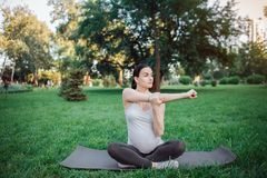 Nice young pregnant woman sit on yoga mate outside in park. She stretch her arm and look forward. Model sit in lotus stock photos
