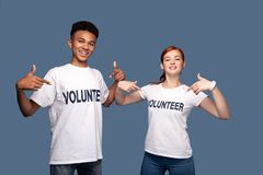 Nice young volunteers pointing at themselves. We help people. Nice young volunteers smiling while pointing at themselves royalty free stock photos