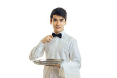 Nice young waiter holding a tray with a towel and improves hand tie neck. On white background Royalty Free Stock Photo