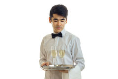 Nice young waiter lowered his eyes down and holding a tray with two glasses of wine Stock Photos