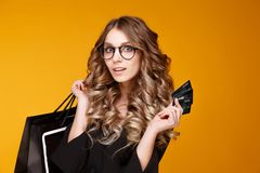 Nice young woman in a black dress and cristal-clear glasses posing with black credit cards royalty free stock photo