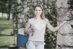Nice young woman holding horticultural tools in garden. On sunny day Stock Images