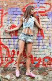 Nice young woman in jeans suit near brick wall royalty free stock photo
