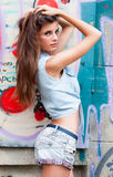 Nice young woman in jeans suit near brick wall royalty free stock photos