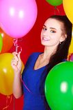 Nice young woman among many bright balloons Royalty Free Stock Photo