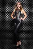 Nice young woman posing in the studio. Dressed in a black leather suit royalty free stock photos