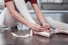 Nice young woman putting on her ballet shoes stock images