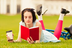 Nice young woman reading a book and enjoying a coffee Royalty Free Stock Photos