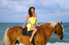 Nice young woman riding a horse. On the beach Royalty Free Stock Images
