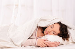 Nice young woman sleeping on white bed Royalty Free Stock Photography