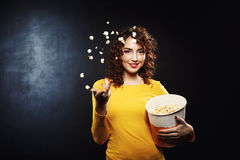 Nice young woman throwing popcorn up in the air smiling. Nice young woman throwing tasty popcorn up in the air looking straight with cheerful smile Royalty Free Stock Photo