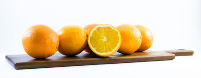 Nicely colored oranges on a white background - front and back lined next to each other on a wooden board Royalty Free Stock Photos