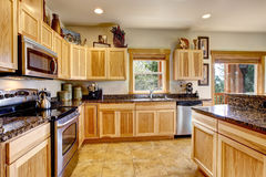 Nicely decorated kitchen room interior with modern cabinets and tile floor. Also granite counter tops and built-in steel appliances Stock Photos
