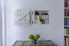 Free Nicely Decorated Small Bookshelf With A Shabby Wooden White Shutter In A Room Of A Country House Royalty Free Stock Image - 176907736