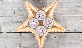 Nicely decorated sushi rolls. Served on the back of a starfish on a wooden table Stock Photography