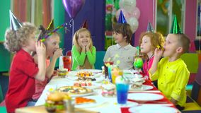 Kids in colorful hats are celebrating birthday at entertainment center. Nicely dressed kids in colorful hats celebrating birthday of their friends at children`s stock video