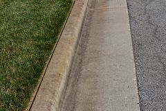 Nicely edged green grass alongside a formed concrete curb. Horizontal aspect stock photo