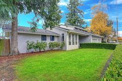 Nicely remodeled home exterior with boxwood hedge. Plus two garage spaces Stock Image