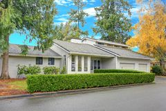Nicely remodeled home exterior with boxwood hedge. Plus two garage spaces Royalty Free Stock Photo