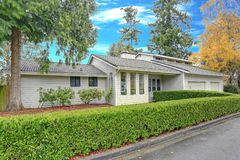 Nicely remodeled home exterior with boxwood hedge. Plus two garage spaces Stock Photo