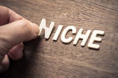 Niche Wood Letters. NICHE, closeup hand place a wood letter into the word for niche concept royalty free stock photos
