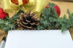 Nicht abgeschlossene Liste von Zielen in einem Notizbuch auf einem Holztisch mit Weihnachtsdekorationen und einem Laptop stockbilder