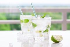 Nicht Alkohol kaltes mojito Cocktail mit frischem Kalk, Minze und zerquetschtem Eis auf einer weißen Tabelle Lizenzfreies Stockbild