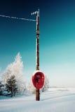 Nicht benutztes rotes Telefon, das auf dem Wintergebiet hängt Lizenzfreie Stockfotografie