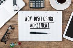 Nicht--diclosure Vereinbarung über Notizbuch auf Schreibtisch mit Computer Lizenzfreie Stockfotografie