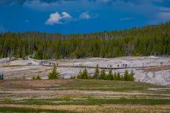 Nicht identifiziert, das alte zuverlässige Ausbrechen in Yellowstone Nationalpark auf einer Promenade peoplewalking umgeben durch stockfotografie