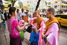 Nicht identifizierte Anfängermönche der jungen Frauen, die Morgenalmosen in Ya gehen lizenzfreie stockbilder