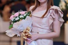 Nicht identifizierte attraktive Frau, die einen Blumenstrauß von schönen Blumen in ihren Händen hält Liebes- und Romancekonzept Stockbild