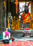 Nicht identifizierte Frau beten nahe buddhistischem Altar stockfotografie