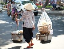 Nicht identifizierte Frau trägt Bambusjoch mit Nahrungsmitteln für Verkauf auf der Straße von Saigon, Vietnam Lizenzfreie Stockfotos