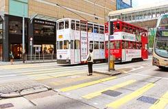 Nicht identifizierte Frauen, die warten, um eine verkehrsreiche Straße in Hong Kong zu kreuzen Lizenzfreie Stockfotos