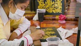 Nicht identifizierte Frauenfarbe auf hölzernem Stück für Lackplatte Die Kunst von Khmerlack-Arbeit origi stock footage