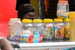 Nicht identifizierte ghanaische Frau sitzt hinter Süßigkeitszähler lizenzfreie stockfotos