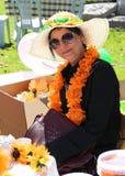 Nicht identifizierte hübsche Frau mit dem Hut, der am orange Blüten-Karneval aufwirft Stockfotos