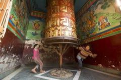 Nicht identifizierte Kinder haben Spaß mit dem Spinnen des großen tibetanischen buddhistischen Gebetsrades bei Boudhanath Stupa Stockbild