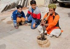 Nicht identifizierte Kinder lachen und betrachten, spielend den Flötenschlangenbeschwörer mit Kobren stockbild