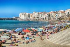 Nicht identifizierte Leute auf sandigem Strand in Cefalu, Sizilien, Italien Lizenzfreies Stockbild