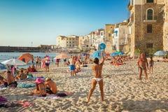 Nicht identifizierte Leute auf sandigem Strand in Cefalu, Sizilien, Italien Stockbilder