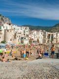 Nicht identifizierte Leute auf sandigem Strand in Cefalu, Sizilien, Italien Lizenzfreie Stockbilder